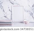 Blank frame and stack of fabrics over marble table 34736551