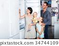 family choosing new freezer in store . 34744109