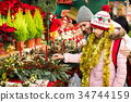 Woman with daughter looking at floral decoration at Cristmas fair 34744159