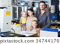 Family of four standing near electronics in household 34744170