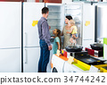 family of four shopping new refrigerator in home appliance store 34744242