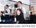Hairdresser cutting hair of teenage 34744262