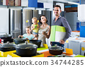 couple with two children picking new kitchenware in home appliances shop 34744285