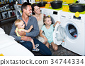 Family shopping washing machine in appliances store 34744334