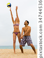 Couple playing with a ball on the beach 34744536