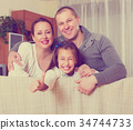 Little girl with parents posing 34744733