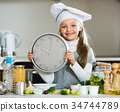 Girl in cook cap holding clock at domestic kitchen 34744789