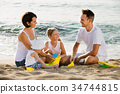 Parents with two kids playing with toys on beach 34744815