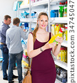 woman choosing detergent at a household goods in the store 34745047