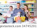 couple and teenager with household goods purchase in the store 34745201