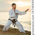 Handsome guy practising karate kata poses 34746494