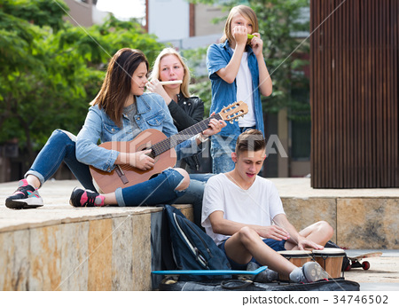Teenagers playing music outdoors . 34746502