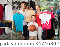 Young positive parents with boy in sport store 34746802
