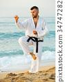 Guy doing karate poses 34747282