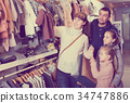 Family with children searching clothes for new baby 34747886