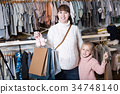 Smiling pregnant woman and child boasting purchases 34748140