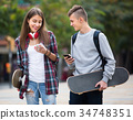 Teenagers with skateboards outdoors . 34748351