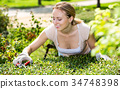 Woman working with green bush using horticultural tools 34748398
