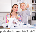 Mother and smiling daughter learning to do paper figurines 34748421