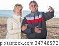 Smiling husband points to something interesting 34748572