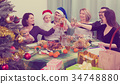 Relatives joyfully celebrate Christmas at table o 34748880