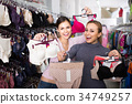 two female customers holding bras and panties in hands in underwear store 34749257