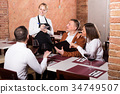 Ordinary female waiter writing down order 34749507