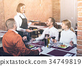 Female waiter bringing order to visitors 34749819