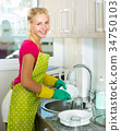 Woman doing dishes at kitchen 34750103