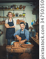 two potters working with ceramics in atelier. 34750350