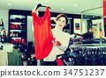 Woman choosing pretty dress 34751237