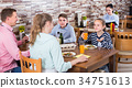 parents and smiling children chatting during dinner in family cafe 34751613
