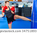 Woman boxer is training kick in box gym. 34751893