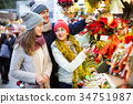 family of three with teenage girl choosing floral decorations at market. Shallow depth of focus 34751987