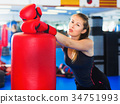 Potrait of woman boxer who is standing near punching bag 34751993
