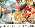 Smiling family of three choosing Christmas star flower 34752486