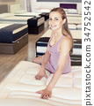 Sexy girl sitting on mattress in furniture store 34752542