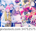 positive parents with teenage girl at counter with Poinsettia and floral decorations 34752575