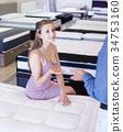 Positive salesman demonstrating to girl mattress 34753160