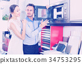 Young husband and wife are choosing new microwave 34753295