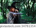 Image of young laughing witch with book 34761354