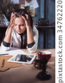 Young frustrated woman working at office desk in 34762220