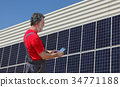 Solar energy, worker and panels 34771188