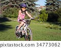 Portrait of a little girl in helmet on a bicycle 34773062