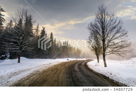 winding road through forest in winter 34807729