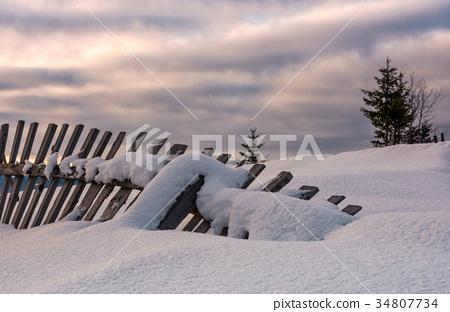 fallen wooden fence on snowy hillside 34807734