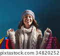 Happy young woman holding shopping bags 34820252