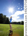 Woman playing golf on field 34820758
