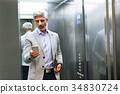 Mature businessman with smartphone in the elevator 34830724