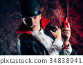 handsome man dressed in a Dracula costume for 34838941